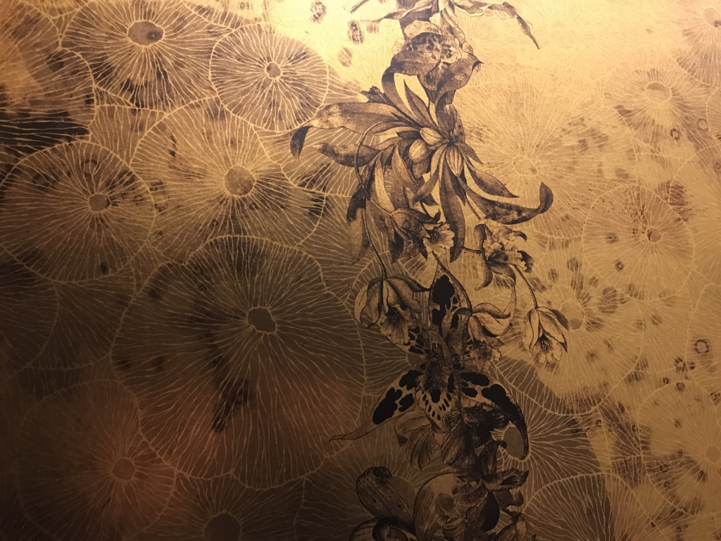 A gold metallic wallpaper up the staircase designed with jellyfish and orchids