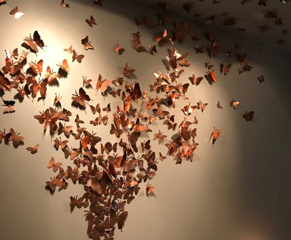 A fluster of copper butterflies flying up the wall onto the ceiling