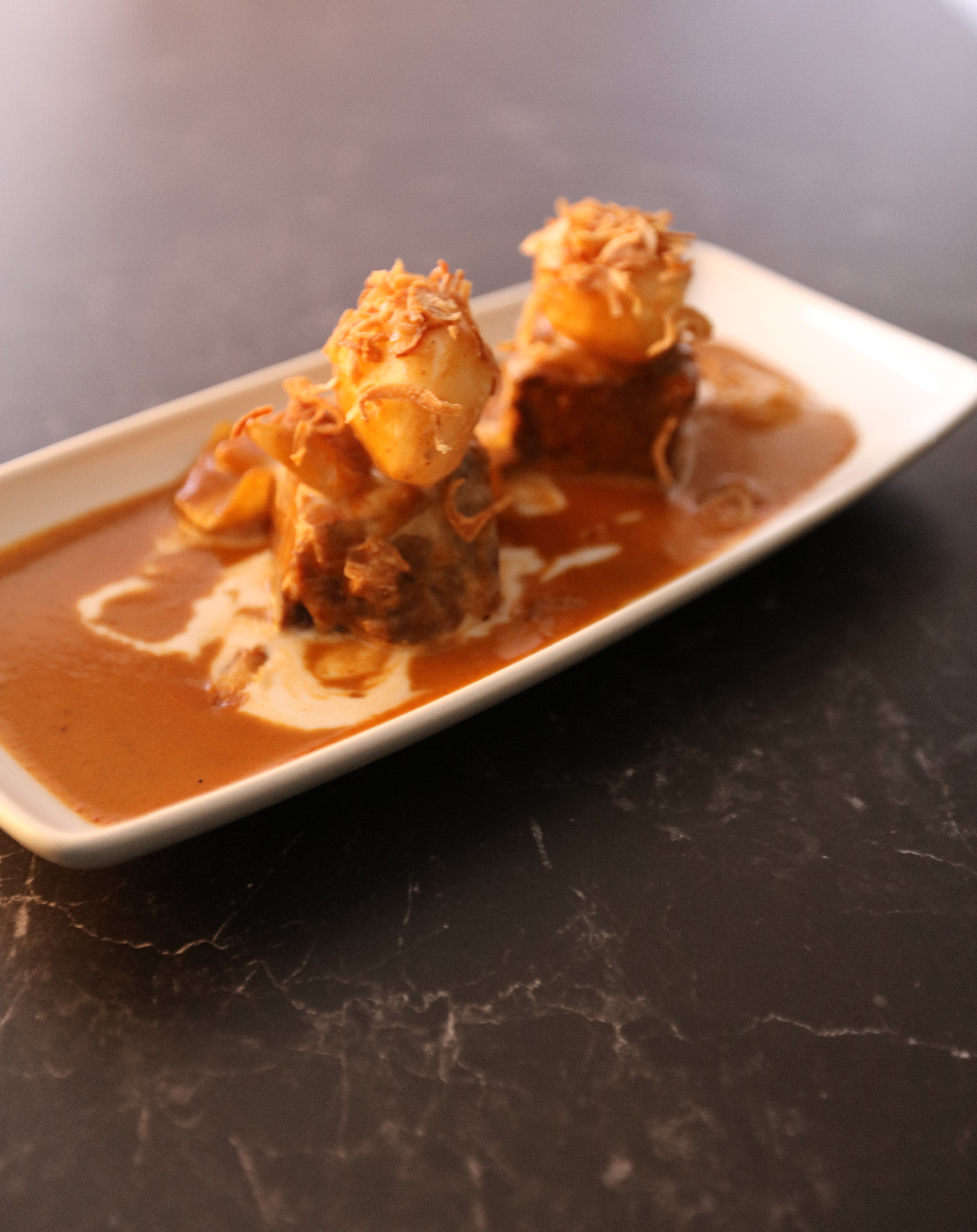 A rectangular plate with two portions of the fillet of beef Masaman curry