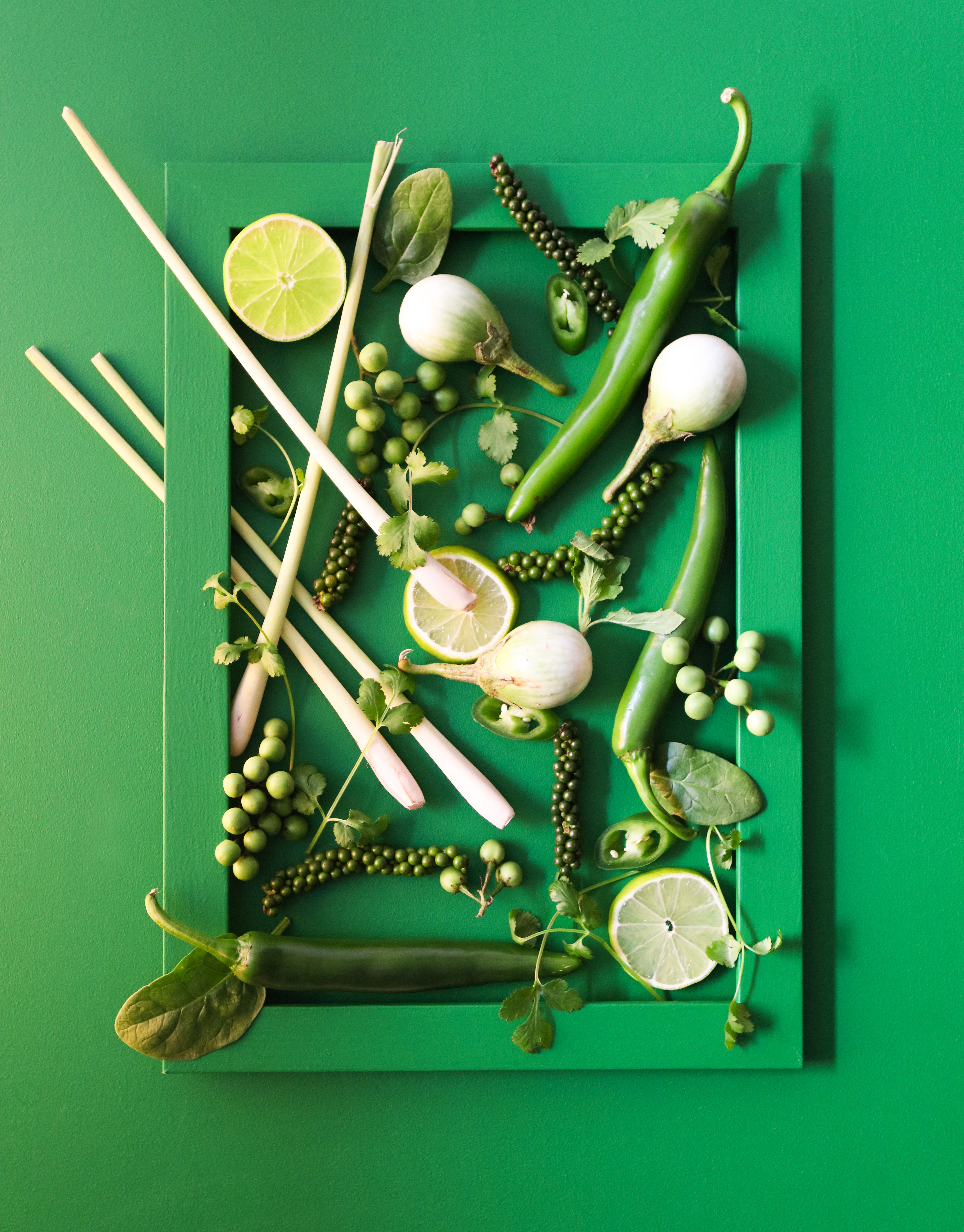 A green frame filled with green thai ingredients such as holy basil to create a framed artwork piece
