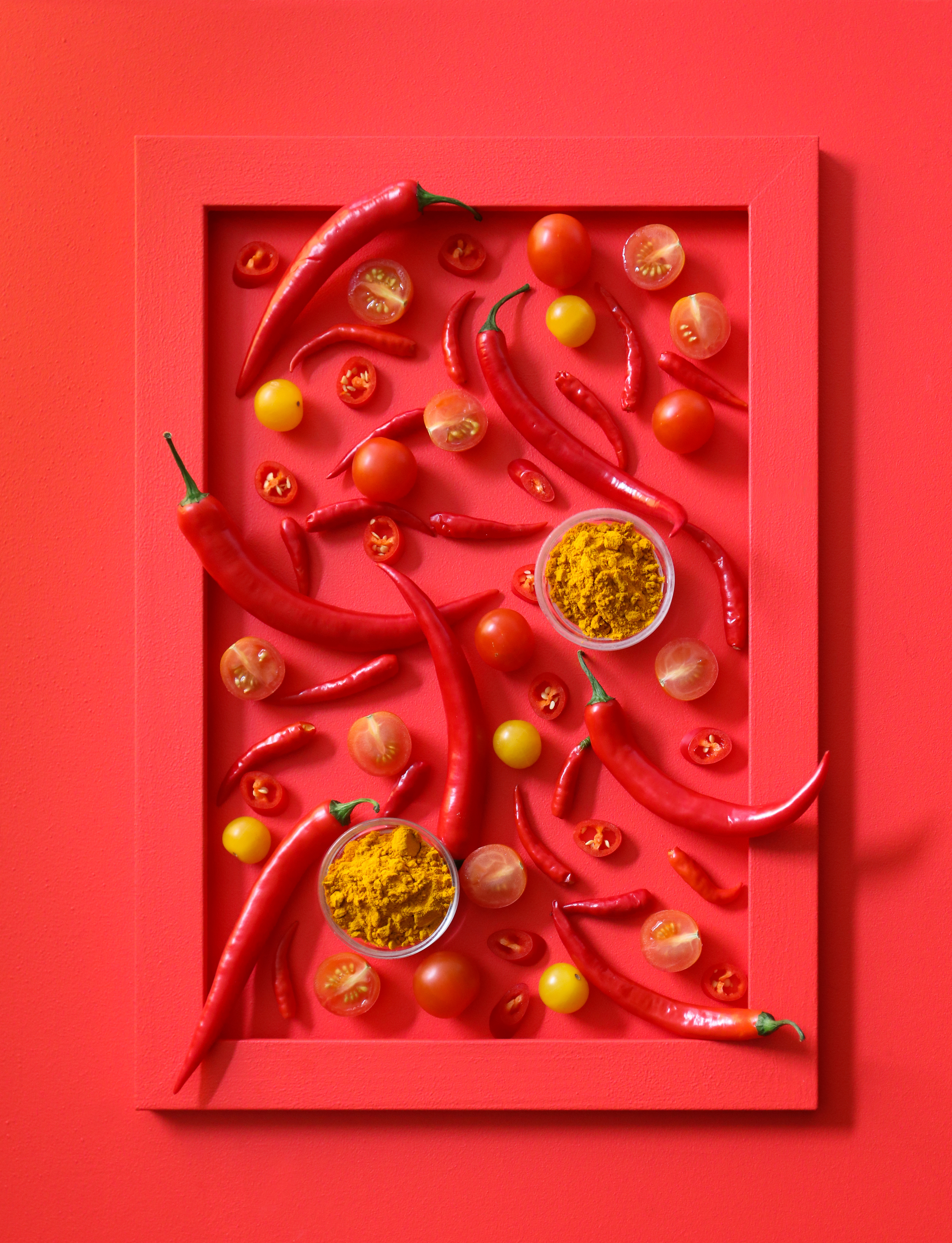 A red frame filled with red thai ingredients such as chillies that created a framed food artwork